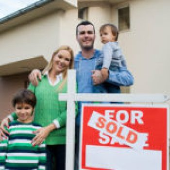 Family of Four In Front of Newly Sold House